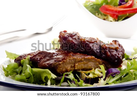 barbecue spare ribs on a plate with fresh salad