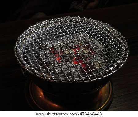 barbecue stove with grill grid over charcoal on fire, low key lighting style