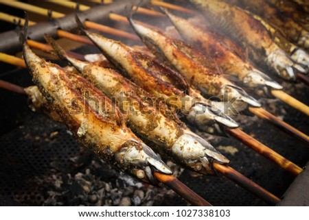 Barbecue with fish. Grilled fish (mackerel) on a stick