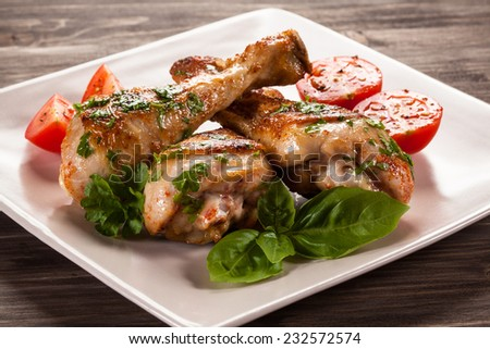 Barbecued chicken legs and vegetables  - stock photo