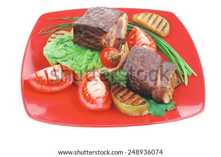 barbecued meat : beef ( lamb ) garnished with baked apples , fresh raw tomatoes, hot pepper, on bread, over red plate isolated on white background - stock photo