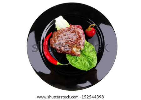 barbecued meat : beef ( lamb ) garnished with green lettuce and red chili hot pepper on black dish isolated over white background
