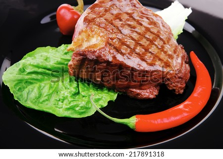 barbecued meat : beef ( lamb ) garnished with green lettuce and red chili hot pepper on black dish isolated over white background - stock photo