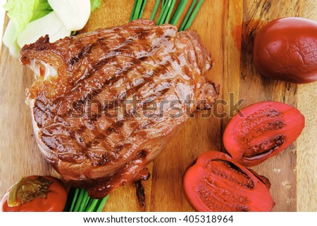 barbecued meat : beef ( lamb ) garnished with green lettuce and red chili hot pepper on wooden plate isolated over white background - stock photo