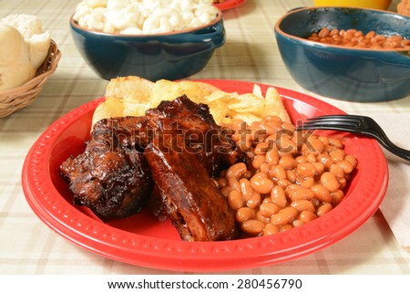 Barbecued pork ribs and baked beans on a picnic plate - stock photo