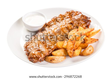 Barbecued pork ribs served with potatoes and mushroom sauce isolated on white background - stock photo