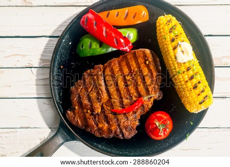Barbecued rib eye beef steak with grilled corn on the cob, colorful peppers and a tomato, served on a skillet on a white wooden table outdoors in sunshine, overhead view - stock photo