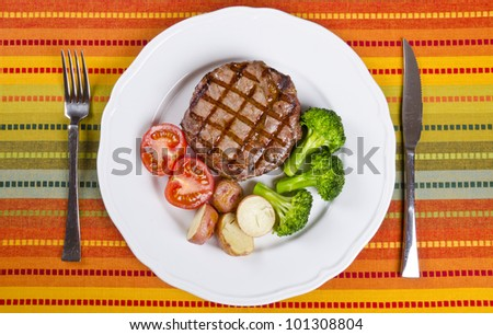Barbecued Rib Eye Steak Served with Broccoli, Potatoes and Tomatoes - stock photo