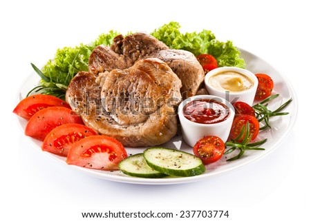 Barbecued steaks and vegetable salad - stock photo