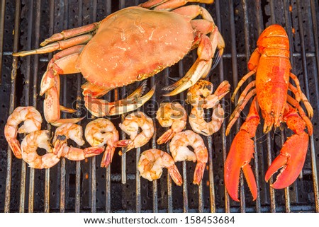 Barbecuing red Lobster, dungeness crab and jumbo Shrimps, shot from above - stock photo