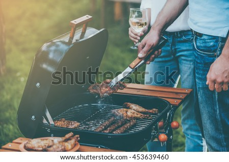 Barbecuing to perfection. Close-up of two people barbecuing meat on the grill while standing outdoors
