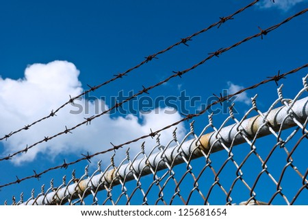 Barbed wire and fence on sky background - stock photo