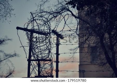 Barbed wire around prison walls - stock photo