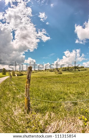 Barbed-wire fence and pasture - stock photo