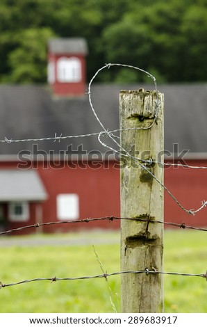 Barbed wire fence at farm with barn in distance.