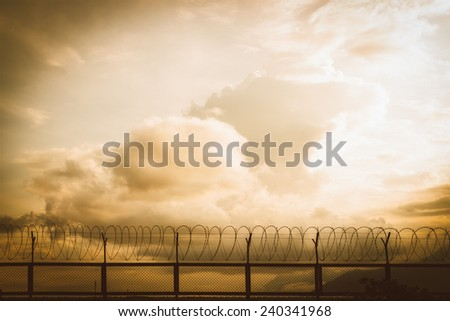 barbed wire fence at sunset - stock photo