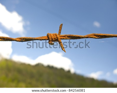 Barbed wire fence, over a blue sky. Detail close up. - stock photo