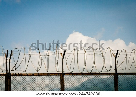 barbed wire fence razor blue sky clouds - stock photo