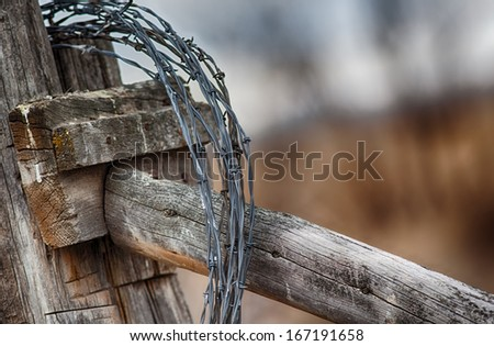 Barbed wire looped around fence post - stock photo