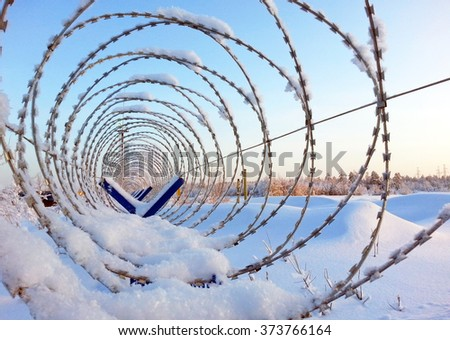 Barbed wire on a fence - stock photo