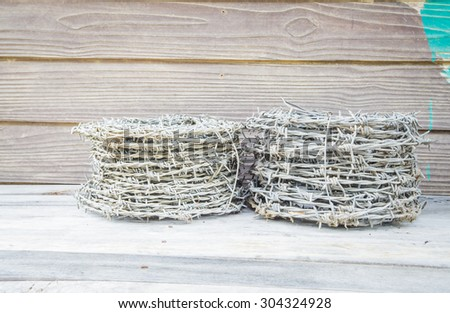Barbed wire  on a wooden surface - stock photo