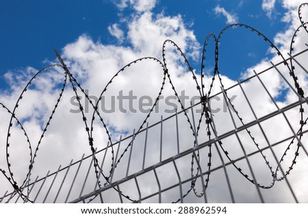 Barbed wire on blue sky background - stock photo