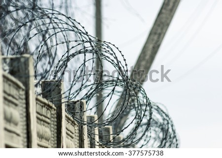 Barbed wire on dark fence.  - stock photo