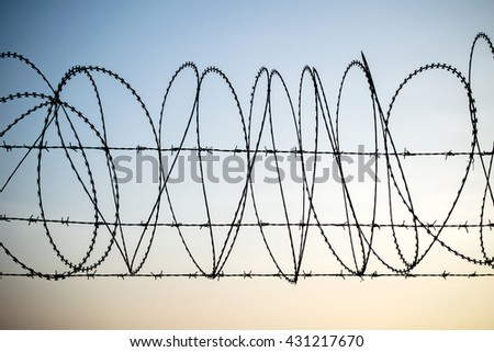 Barbed wire on dark fence. Monochrome silhouette photo, The tangle barb with blue sky - stock photo