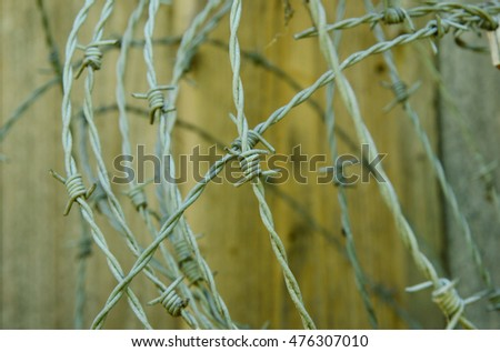 barbed wire on wooden background.