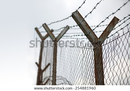 Barbed wire perimeter fencing against a gloomy sky.  - stock photo