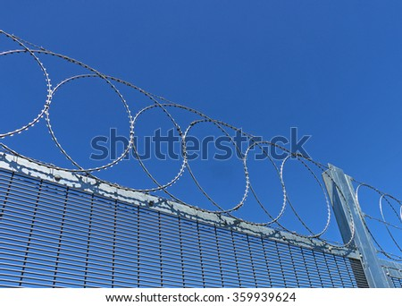 barbed wire topped fence in a blue sky