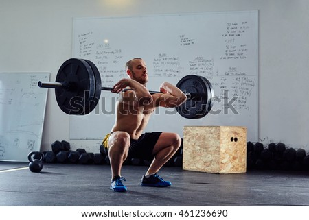 Barbell front squat exercise - athletic man during intense workout at the gym