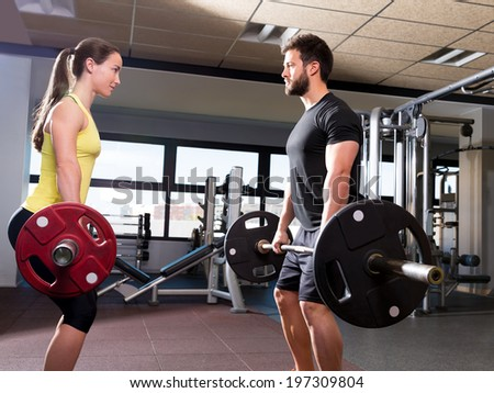 Barbell man and woman workout at fitness gym club - stock photo