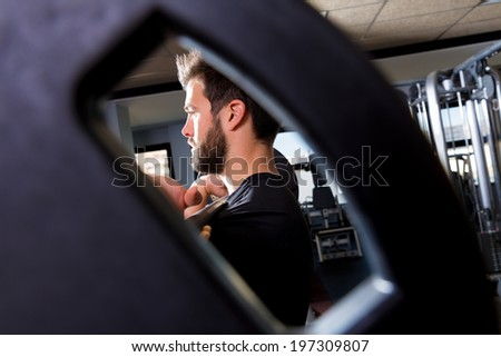 Barbell man weightlifting workout view through a weight bell hole