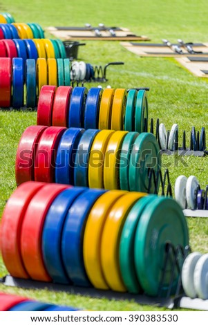 Barbell weight gym equipment on grass - stock photo