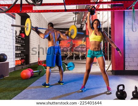 Barbell weight lifting man and woman rising kettlebell gym weightlifting - stock photo