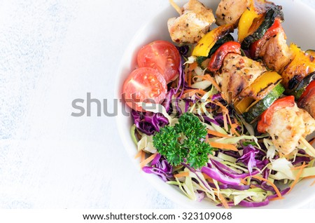 Barbeque chicken kebabs on wooden skewer sticks served with raw side salad coleslaw made of shredded cabbage and carrot - stock photo