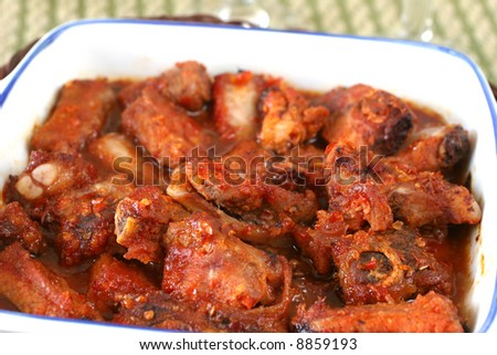 Barbequed oriental spicy pork ribs in white casserole dish