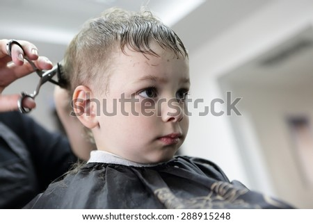 Barber cutting hair of a child at the barbershop - stock photo