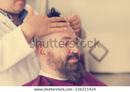 Barber makes a mohawk hairstyle at the adult man with beard. Toned