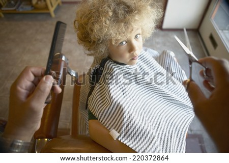 Barber reaching out to cut young boy's hair - stock photo