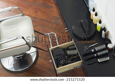 Barber's chair beside open draw of hair products, scissors and hairbrushes in salon, overhead view - stock photo