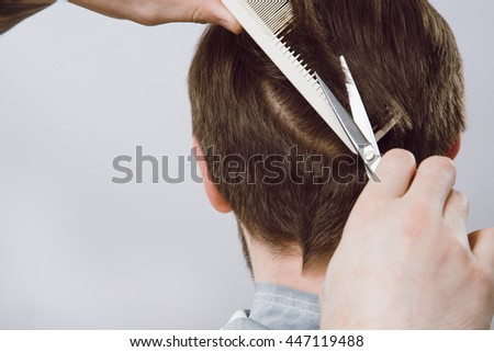 Barber's hands doing a haircut for darkhaired client with scissors and white comb at gray studio background, copy space.
