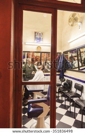 Barber shaves a bearded man in a barber shop in Marrakech, Morocco, 26-02-2015