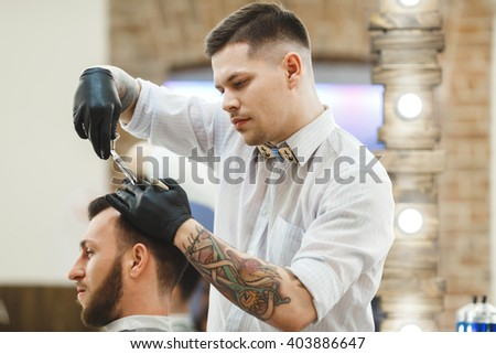 Barber with dark hair and tattoo wearing white shirt and black gloves doing a haircut for client with scissors at barber shop, lights at background, portrait.