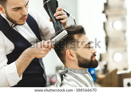 Barber with dark hair wearing white shirt doing a haircut with hair dryer and hair brush for man with black hair at barber shop, mirror at background.