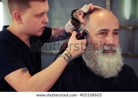 Barber with tattoo making haircut to hipster senior man with beard and working with electric razor