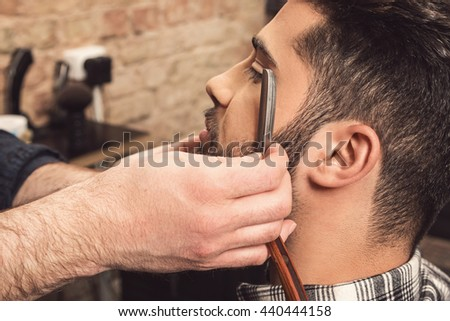 Barber working with a straight razor for shaving beard