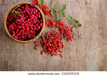Barberry in bowl with leaves and dry goji berries on wooden background - stock photo