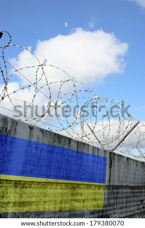 Barbwire and grey wall with ukraine national flag